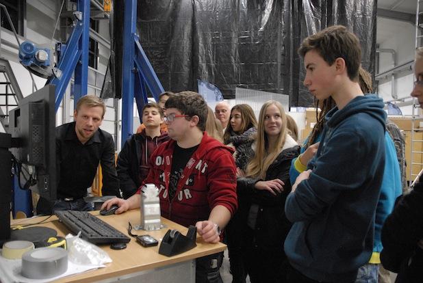 Die Schülerinnen und Schüler schauen sich die Kameraaufzeichnung vom Fallturm-Experiment an. Erläutert wird dieses von Marco Grote (links).